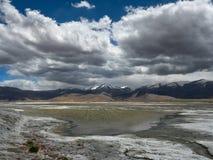 Salt Lake entre las altas montañas, superficie fangosa del agua, costa blanca, en el fondo de la montaña, en la nube de cúmulo en Foto de archivo libre de regalías