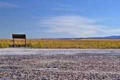 Salt lake rustic seat near grass plantation in a beautiful blue. Sky Stock Photo