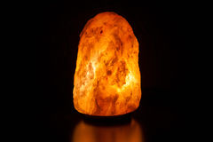 Salt lamp on black background Stock Images