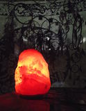 Salt lamp lit in the dark. This beautiful lit salt lamp stands against a leafy tapestry background with he shadows of dream catchers visible in the distance Stock Photos