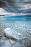 Salt mineral at Dead Sea. A sunrise time ove one of the Dead-Sea shores at winter time. during that morning the sun was behind the clouds which create a Stock Image