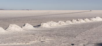 Salt mining in Colchani with salt pyramids, ready for harvest, in the Uyuni salt flat Salar de Uyuni, Bolivia royalty free stock image