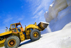 Salt Mining Equipment. Salt mining using heavy equipment. Salt is falling down on the ground. Colorful on a bright sunny day. Wide angle, horizontal Royalty Free Stock Photos