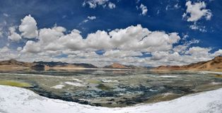 Salt mountain lake: among white stone salt blue water with reflection of white cumulus clouds in a bright sky. Royalty Free Stock Images