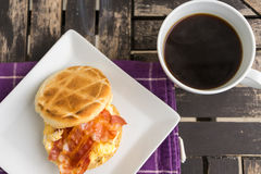 Salt muffin with scrambled eggs, bacon and cheese on white plate Royalty Free Stock Photography