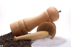 Salt n peppa. A pepper mill with black peppercorns and a mortar and pestle with sea-salt, against a white background Stock Photography