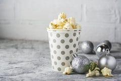 Salt nytt vresigt hemlagat popcorn i silverpappers- kopp i modeljusbakgrunden av den vita tegelstenväggen i ett nytt Royaltyfri Bild