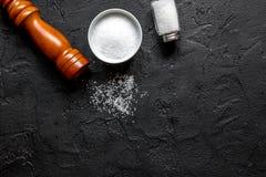 Salt och saltkar på svart modell för bästa sikt för stentabellbakgrund Arkivbild