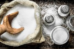Salt in an old bag on a tray. On rustic background Stock Image