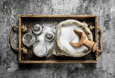 Salt in an old bag on a tray. On rustic background Royalty Free Stock Image