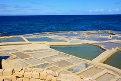 Salt pans along the Marsalforn coastline, Gozo. Salt pans along the waterfront with views out to sea, Redoubt, Marsalforn, Gozo, Malta, Europe Stock Image
