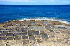 Salt pans along Marsalforn coastline, Gozo. Salt pans along the waterfront with views out to sea, Redoubt, Marsalforn, Gozo, Malta, Europe stock photography