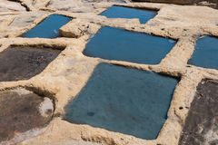 Salt pans, city Marsaskala, island Malta. Holes in rocks at the seaside of the Mediterranean sea, for evaporation the water and getting sea salt. City Marsaskala Stock Photo