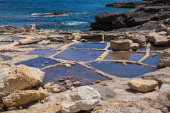 Salt pans, city Marsaskala, island Malta. Holes in rocks at the seaside of the Mediterranean sea, for evaporation the water and getting sea salt. City Marsaskala Stock Images