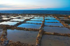 Salt pans cut into the rock on the coast. With the horizon in the background stock images