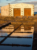 Salt Pans in Fuerteventura, Canary Islands. Workshop building reflected in the salt pans at Salinas del Carmen at sunset. Fuerteventura, Canary Islands royalty free stock photography