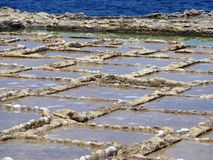 Salt pans in geometric patterns by the ocean stock photography