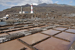 Salt Pans, La Palma, Canary Islands. Salt pans with two lighthouses and volcanic mountains behind. The salt is packaged and sent to supermarkets and shops on the Stock Photo
