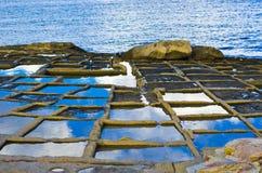 Salt pans in Marsaskala. Scenic view of blue sky and cloudscape reflected on salt pans on coastline of Marsaskala, Malta Stock Image