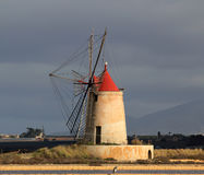 Salt pans and mill. Old windmill in the province of Marsala - Sicily Royalty Free Stock Photos