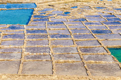 Salt pans near Qbajjar in Gozo, Malta. Salt evaporation ponds, also called salterns or salt pans located near Qbajjar on the maltese Island of Gozo Royalty Free Stock Photos
