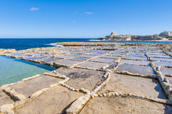 Salt pans near Qbajjar in Gozo, Malta. Salt evaporation ponds, also called salterns or salt pans located near Qbajjar on the maltese Island of Gozo Stock Images