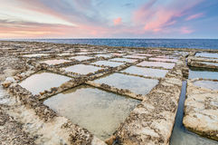 Salt pans near Qbajjar in Gozo, Malta. Salt evaporation ponds, also called salterns or salt pans located near Qbajjar on the maltese Island of Gozo Stock Photography