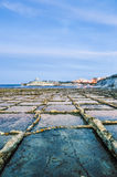 Salt pans near Qbajjar in Gozo, Malta. Salt evaporation ponds, also called salterns or salt pans located near Qbajjar on the maltese Island of Gozo Royalty Free Stock Photography