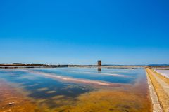 The salt pans of Trapani in the beautiful Italian region of Sicily in the summer, landscape with a tower royalty free stock images