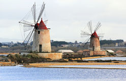 Salt pans and windmills. Old windmills in the province of Marsala - Sicily Royalty Free Stock Images