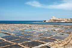 Malta and Gozo islands. Salt pans and yellow sandstone rocks at the sea near to Marsalforn, Gozo island, Malta Royalty Free Stock Photo