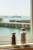 Salt and papper shaker s at ocean view restaurant window Royalty Free Stock Photos