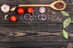 Salt, peppar, vitlök, lök, lager och en sked på en svart woode Arkivbilder