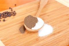 Salt and pepper. On wooden spoon Stock Photography