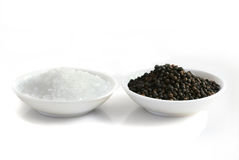 Salt and Pepper. Sea salt and black peppercorns, each in a small white dish. Isolated on white, with high-key effect Royalty Free Stock Photography