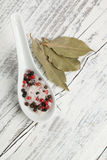 Salt and pepper. Spoon of salt and pepper with bay-leaf on white wooden table Stock Images