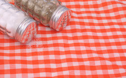Salt and Pepper. Shakers on Orange and White Table Cloth Stock Photos