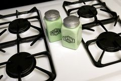 Salt and Pepper. Antique salt and pepper shakers on a stove royalty free stock photography