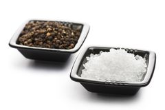 Salt and pepper. Into black bowls, on white background stock photography