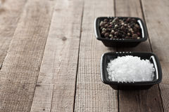 Salt and pepper. 2 bowls with sea salt and peppercorns Stock Photos