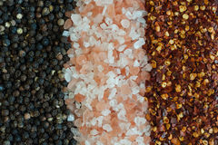 Salt, pepper and chili pepper flakes background Stock Image