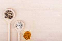 Salt, pepper and curry in spoons on wooden background. Salt, pepper and curry in wooden spoons on wooden background Royalty Free Stock Photo