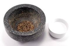 Ground black pepper and salt. Ground pepper in granite mortar and salt in white bowl on white background royalty free stock photo