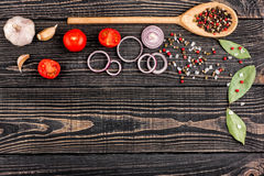 Salt, pepper, garlic, onion, laurel and a spoon on a black woode. N background, top view Stock Images