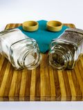 Salt and pepper in a glass shaker and pepper shaker stand on a cutting board stock photo