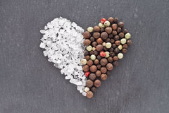 Salt and pepper heart. Heart of sea salt and peppercorns Stock Photography