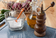 Salt, pepper mill, and olive oil. A kitchen scene as a cooking session is about to begin. Basic ingredients are prepped and ready: salt, pepper, olive oil, with Royalty Free Stock Photo