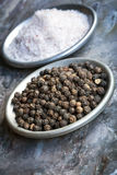 Salt and Pepper. Peppercorns and salt flakes, in small dishes over slate background Stock Images