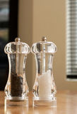 Salt and pepper pots on kitchen table Royalty Free Stock Photography
