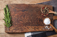Salt, pepper and rosmarinus. Salt, pepper in wooden spoons and rosmarinus on wooden cutting board, top view Stock Image